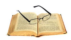 Glasögon vilar på gammal upplaga av Topelius Boken om vårt land.