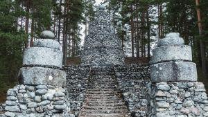 Stor stenkonstruktion med trappa i mitten, överst ett torn fyllt av sten och infogade kvarnstenar här och var.