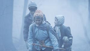 Tre barn promenerar genom en tjock dimma.
