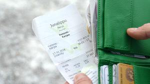 En tågbiljett vid en grön plånbok.