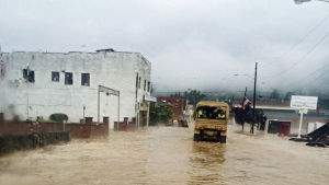 Arme'bil kör längs översvämmad gata.