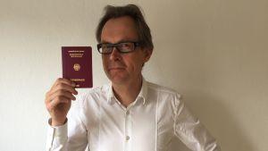 Kaj Arnö i vit skjorta och med tyskt pass i handen som han håller upp.