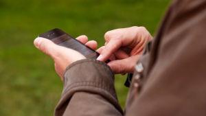 Händer och smarttelefon.