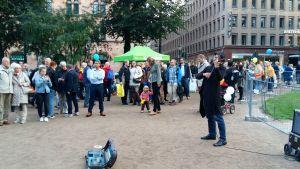 I Esplanadparken står det gatumusikanter eller andra artister, parken är full med folk.