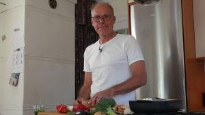 Kocken Paul Reuter skär grönsaker i sitt kök