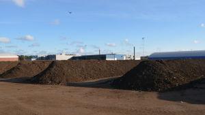 Långa rader av jord ligger utanför bioavfallsanläggningen.