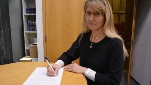 Kvinna skriver under ett papper.