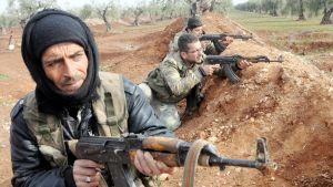 Syriska rebeller som deltar i den turkiska operationen i norra Syrien tar skydd bakom en sandhög.