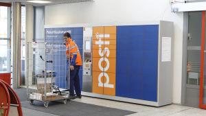 Postanställd plockar in paket i paketautomater.