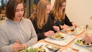 Frida Burgmann, Amanda Juselius och Emma Heiseler äter fiskbullar och potatis i Källhagens skolas matsal i Virkby.