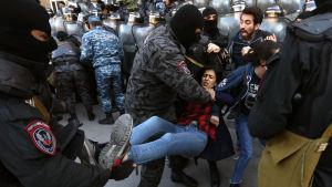 Polisen i Jerevan försöker gripa en demonstrant.