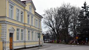 Ett gult gammalt stenhus i två våningar. Till vänster en lekpark.