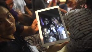 En glad släkting till en av fotbollspojkarna visar ett foto på pojkarna som tagits av räddningsdykare.