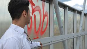 Person iklädd vit skjorta ser bortåt längs med en nerklottrad gångbro.