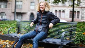 Lisa Gerkman ler mot kameran medan hon sitter på en bänk.