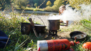 Matlagning ute i naturen. I förgrunden syns en liten bensinflaska som är kopplad till ett sorts spritkök. Ovanpå ligger en kastrull som det ryker ur. I bakgrunden syns en kvinna.