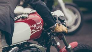 Man i kostym intill motorcykel.