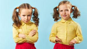 Två identiska tvillingarflickor i likadana kläder
