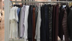 Kläder hänger på en klädstång utanför en butik.