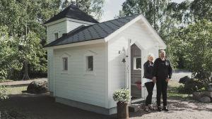 Pieni valkoinen kirkko, edessä pariskunta