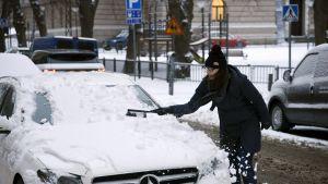Kvinna borstar bort snö från sin bil.