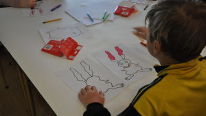 Ett barn ritar en figur på ett papper.