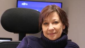 En kvinna i 50-årsåldern sitter i en kontorsstol. Bakom henne skymtar en tv-skärm.