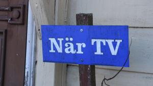 En blå skylt med texten När TV.