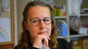 Diakon Kaisa Söderholm, en dam med blå tröja och glasögon med mörka skalmar.