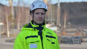 En man med hjälm och gula, neonfärgade arbetskläder på ett hamnområde.