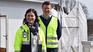 Mikaela Pappila och Mikael Jensen står på taket till ena flygeln på Amos Anderssons sommarresidens. Båda har vita hjälmar på huvudet och gula västar.