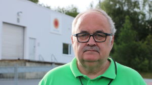 En man med grått hår, mustasch och glasögon står på en fabriksgård.
