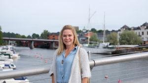 En kvinna står på en gångbro med åstranden i Borgå i bakgrunden.