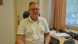En man i en vit skjorta sitter bakom ett skrivbord och ser in i kameran.