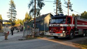 En branbil kör förbi nybyggda hus