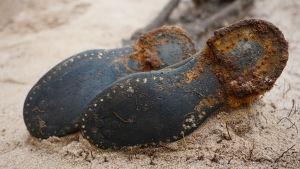 Ett par gamla stövlar ligger i sanden.