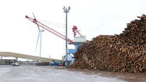 En hög med massaved står på kajen i hamnen i Kristinestad. I bakgrunden syns en stor kran samt ett vindkraftverk.