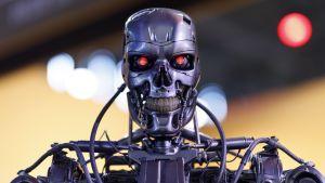 En robot med hotfullt röda ögon visar tänderna i ett onskefullt smil.