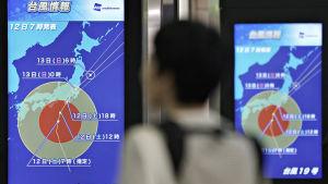 En tågpassagerare tittar på en väderprognos som visar tyfonen Hagibis rörelser på Shinjuku-tågstationen i Tokyo lördagen den 12 oktober.