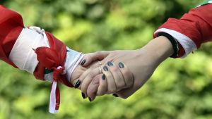 Två par händer med svartmålade naglar håller i varandra.