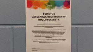 Ett certifkat med regnbågsfärger längst upp, upphängt på väggen i Kampens servicecentral.