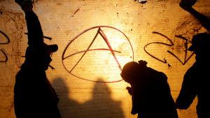 Kolme tummaa hahmoa seinään maalatun anarkistien tunnuksen edessä.