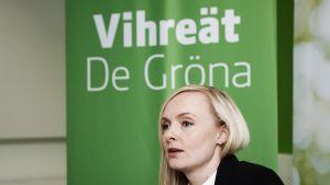 Maria Ohisalo i förgrunden, i bakgrunden en affisch med texten Vihreät De Gröna.