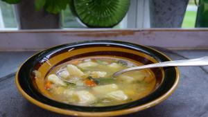 En portion med grönsaksoppa på en tallrik i ett kök