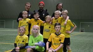 Pojkar 11-laget från ÅIFK står tillsammans med sina tränare på en konstgjord gräsplan inomhus.