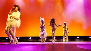 Fyra sångare i vita vilda västern-munderingar dansar mot en solnedgångsfärgad bakgrund.