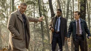 Benoit Blanc (Daniel Craig) står i skogen tillsammans med poliserna Elliott (LaKeith Stanfield) och Trooper Wagner (Noah Segan) och försöker kolla fotspår i leran.