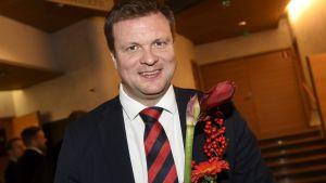 Ville Skinnari (SDP) ler mot kameran med blommor i händerna.