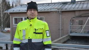 En man med gula arbetskläder står framför en kanal med vatten.