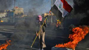 En demonstrant i Najaf, cirka 160 kilometer söder om Bagdad, bar på Iraks flagga bland brinnande bildäck på måndagen.